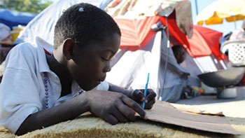 A boy draws at a makeshift camp in Champ de Mars in Port au Prince on January 25, 2010.