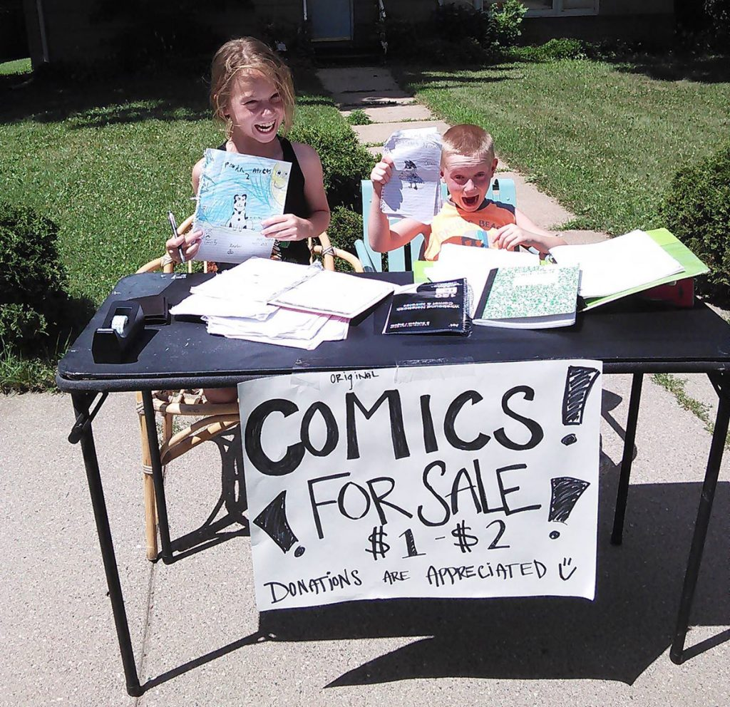 Comics for sale: Two kids and their comic book stand.