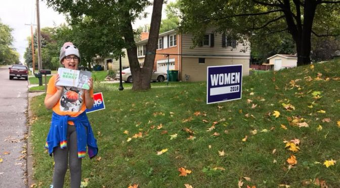 "Holding campaign literature next to a ""Women 2018"" sign."