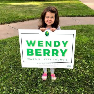 Child with a Wendy Berry yard sign